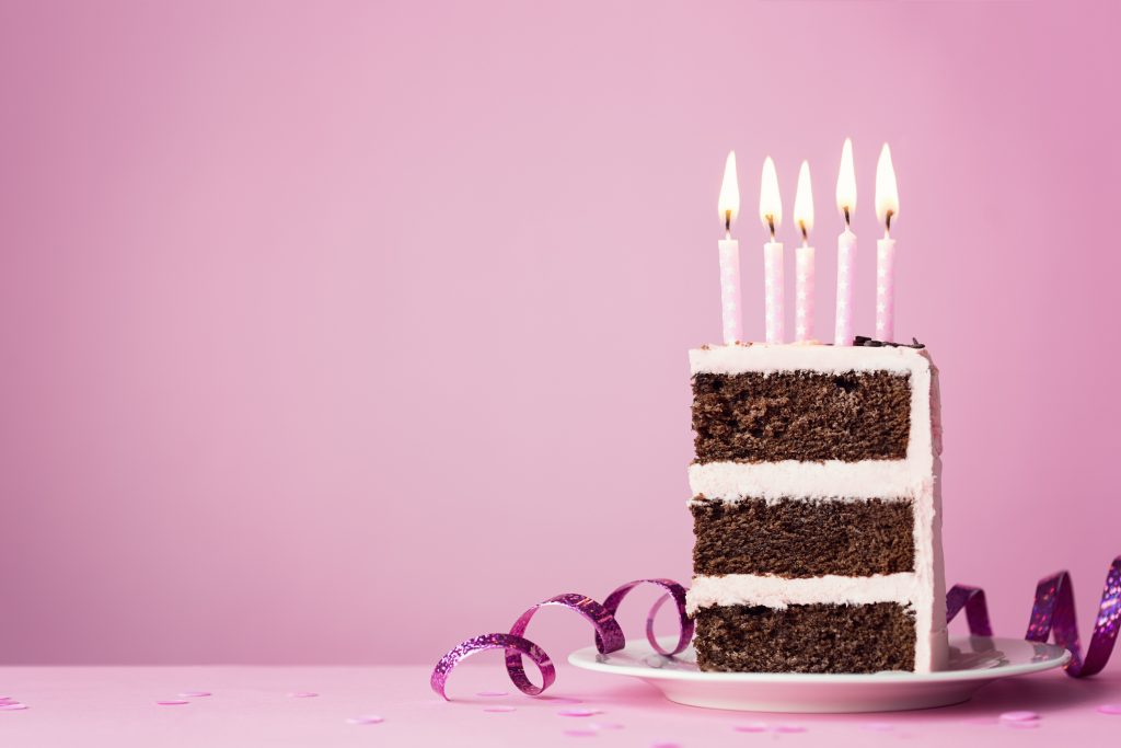 Chocolate birthday cake with purple frosting and candles.