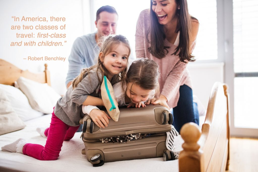 Portrait of a young happy family with two children packing for holiday at home.