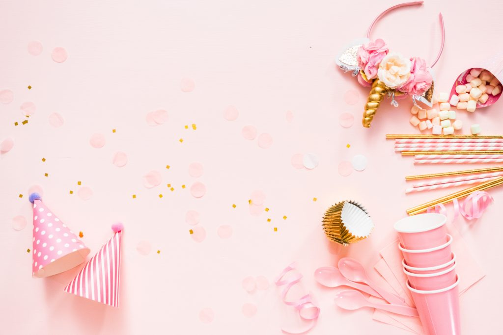 Birthday party for 3 year old on pink flat lay.