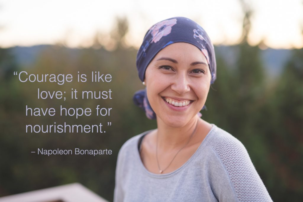 A woman wearing a head wrap looks toward the camera and smiles with hope.