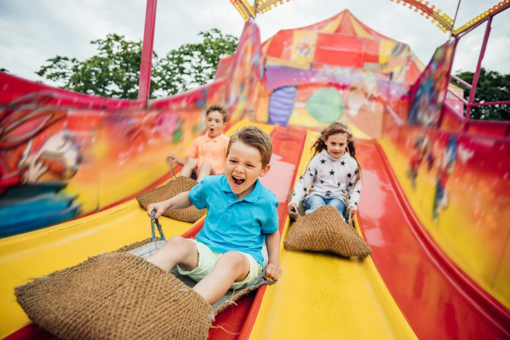 Children having fun sliding down a yellow and red slide while sitting in burlap sacks at a fair.
