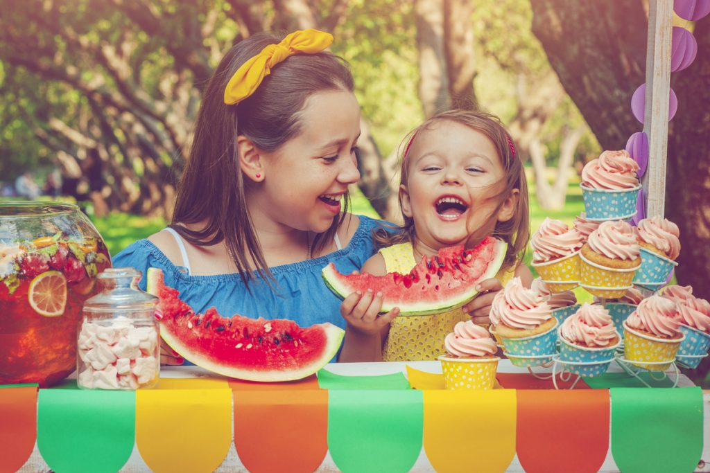 Two sisters having fun outdoors in summer with watermelon, sweets and cupcakes.