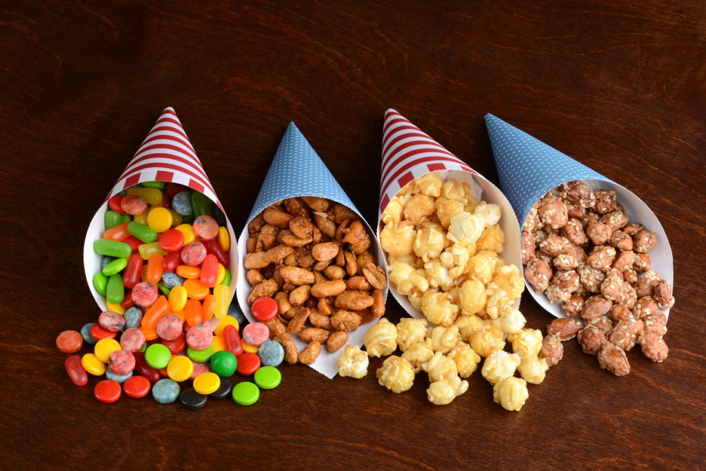 Assorted candies in paper cones on a wood table top.