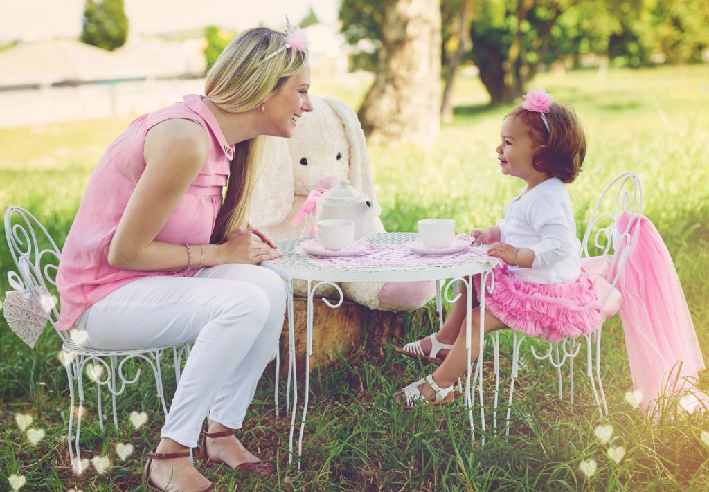 Shot of a mother and her cute little girl having a tea party on the lawn outside for a birthday.
