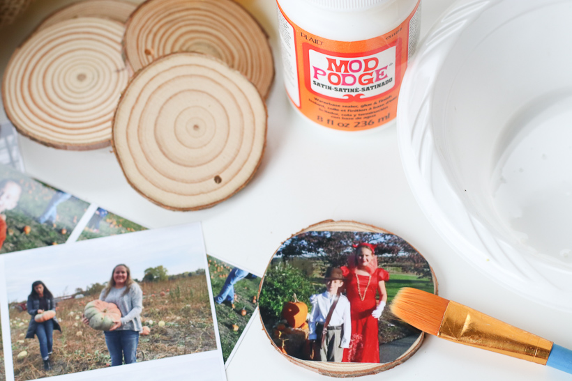 Gluing the photos for a DIY fall wreath for your front door.