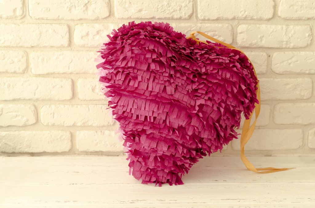 Pink paper heart piñata for bachelorette party.