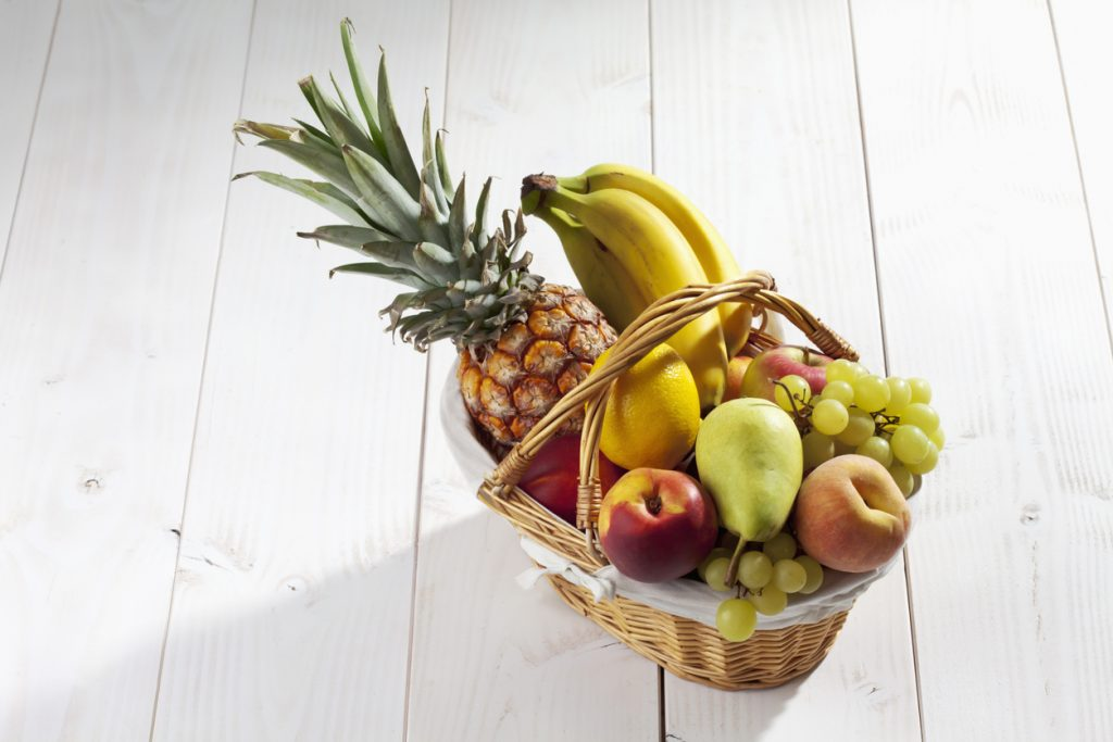 Fruit basket with pineapple, bananas, lemon, apple, peaches, grapes on white wooden background.