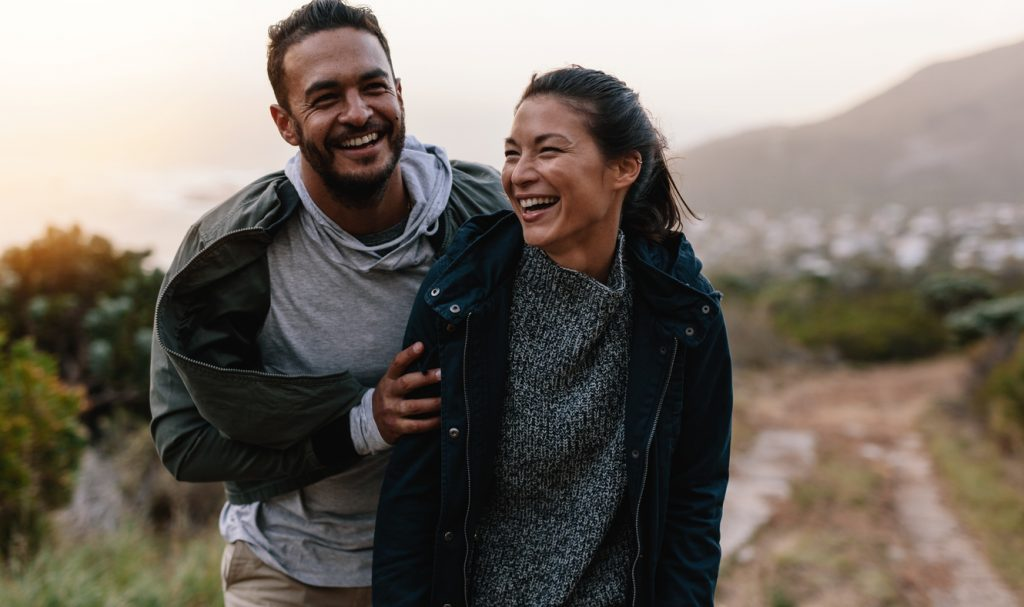 A young couple in love laughs on a hike.