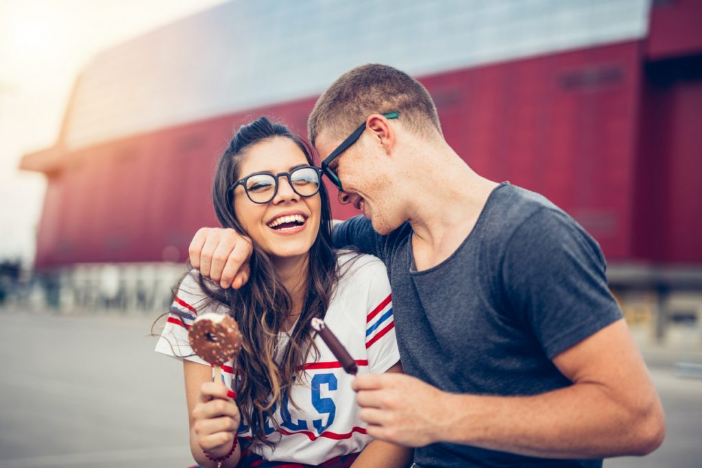 Young couple laughs and eats ice cream outdoors.
