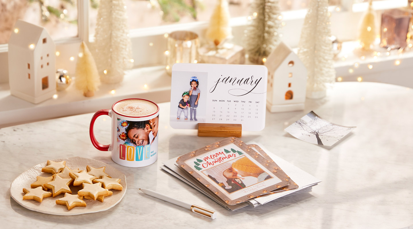 Holiday stationery, cookies and hot cocoa on a kitchen counter.