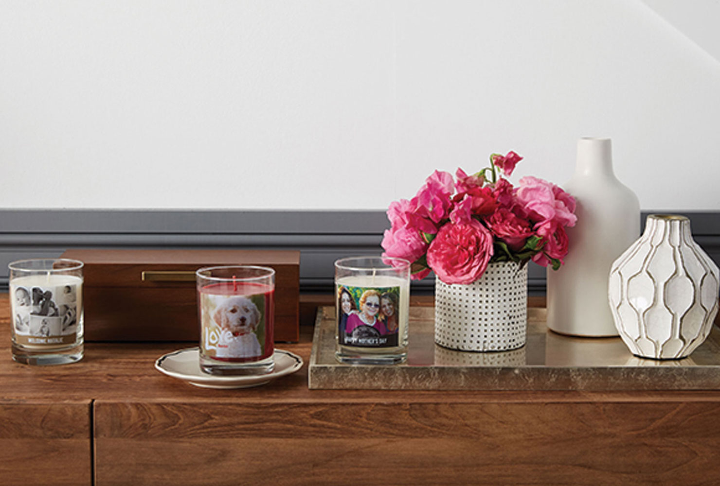 Candle collection and decor on wood table.
