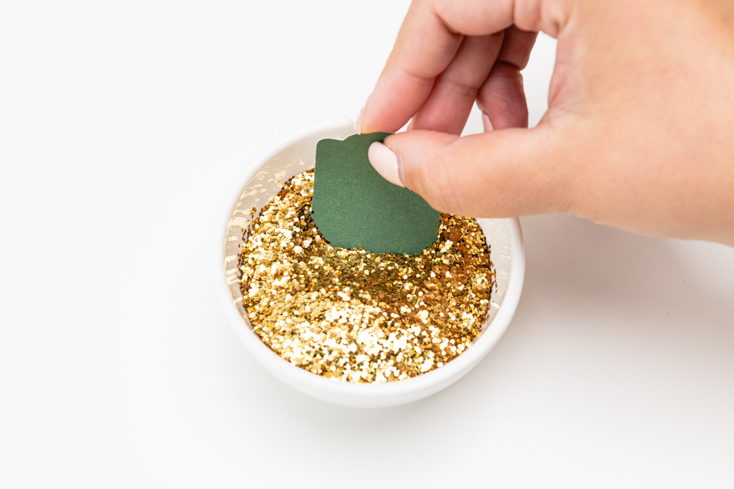 someone dipping the gift tag into a bowl of gold glitter.