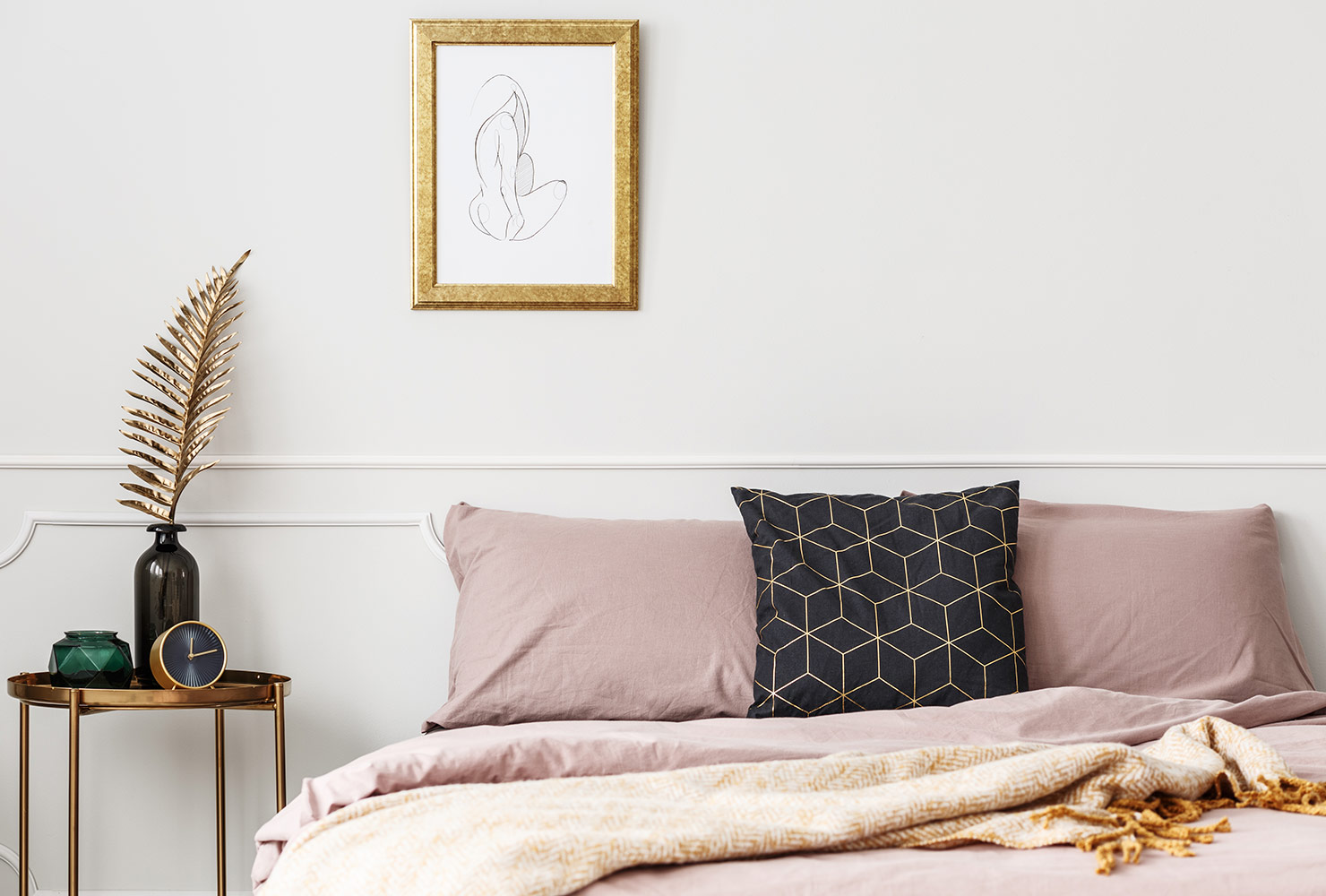 Bedroom with pink bedding and gold accent wall art.