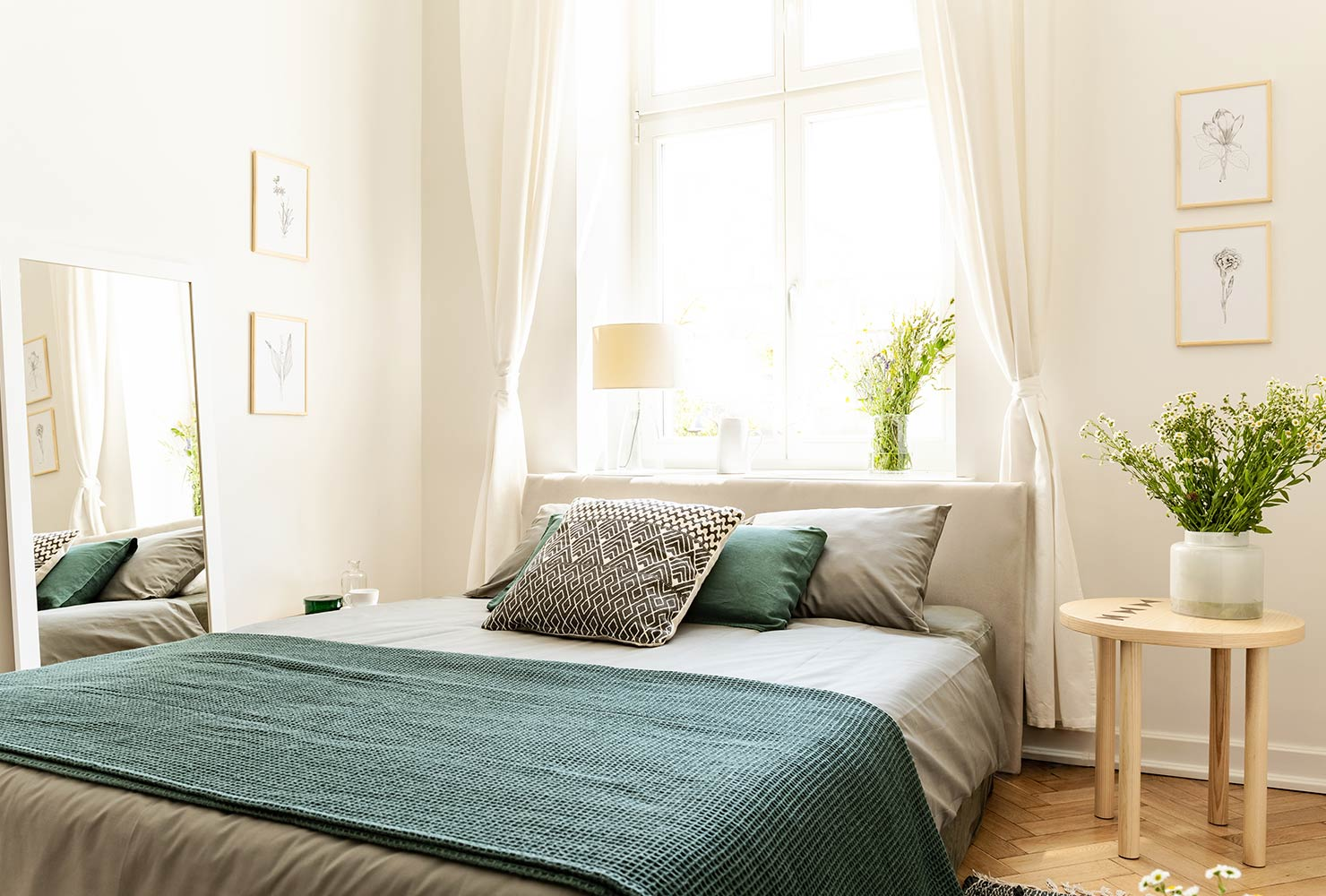 Tan colored bedroom with green bed and plant.