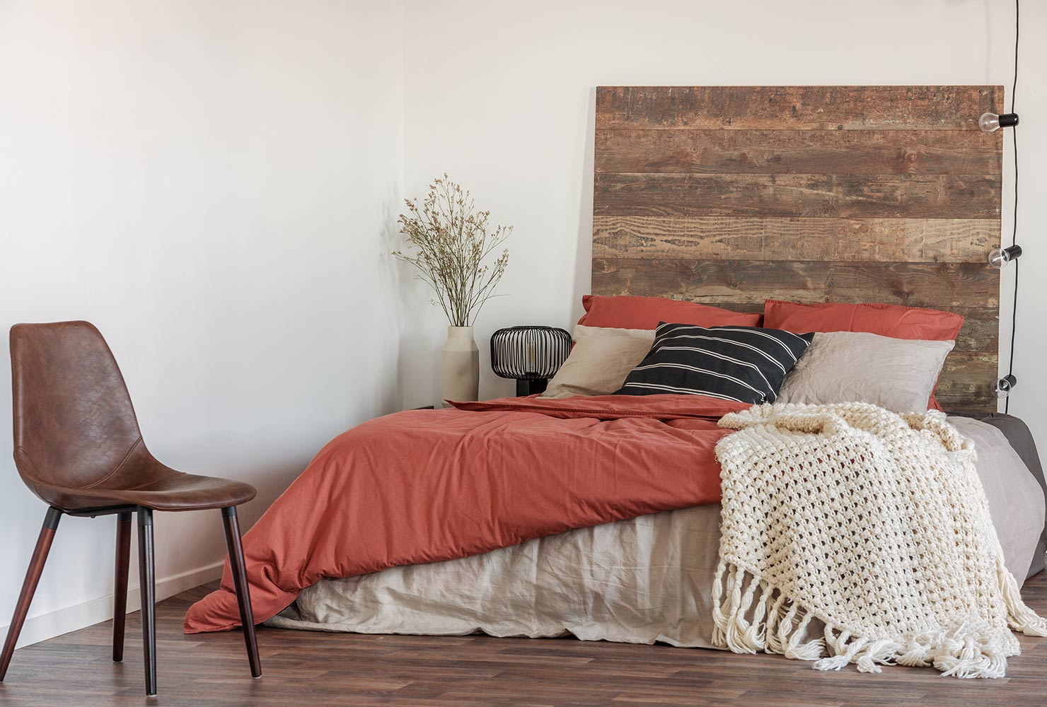 Rustic red bedding with wood headboard.