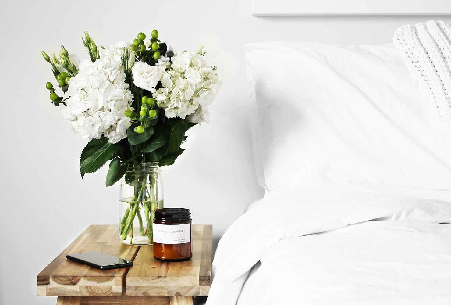 White flowers next to white bed.
