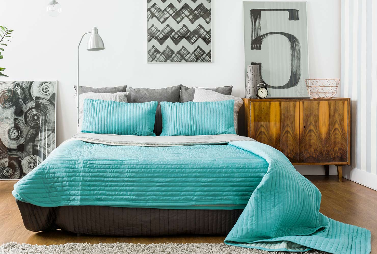 Turquoise bed with wall decor above bed.