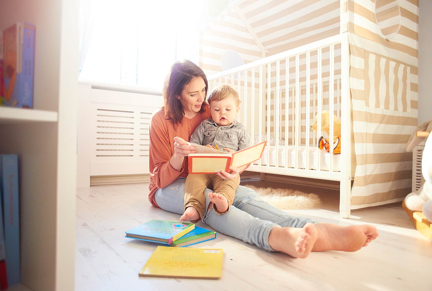 Mom and son sitting on floor by crib reading book.