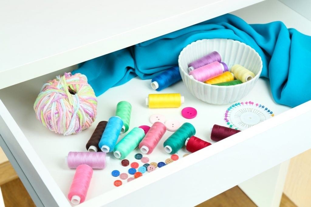 Sewing accessories in open drawer close up.