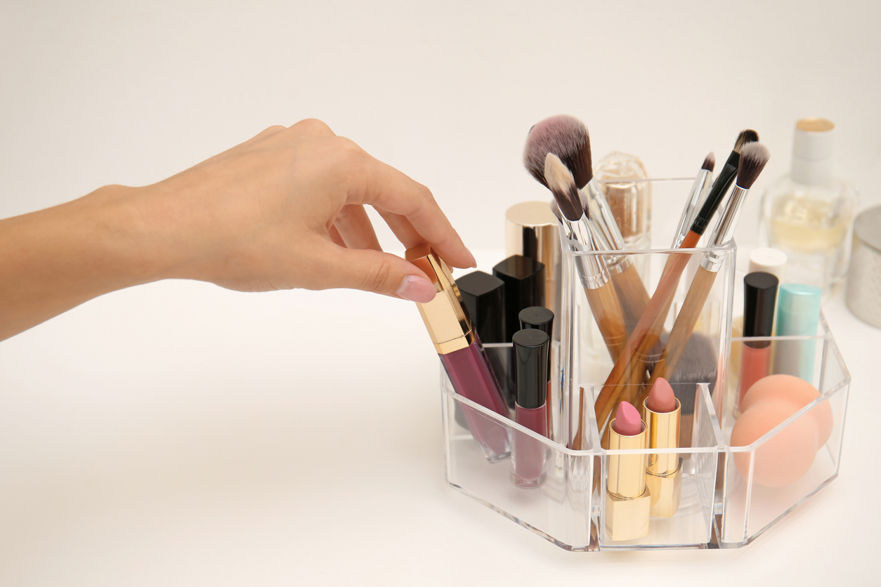 Woman taking lip gloss from organizer for makeup cosmetic products on dressing table