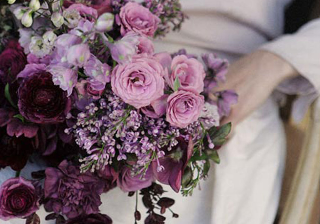 Wedding bouquet with various purple flowers.
