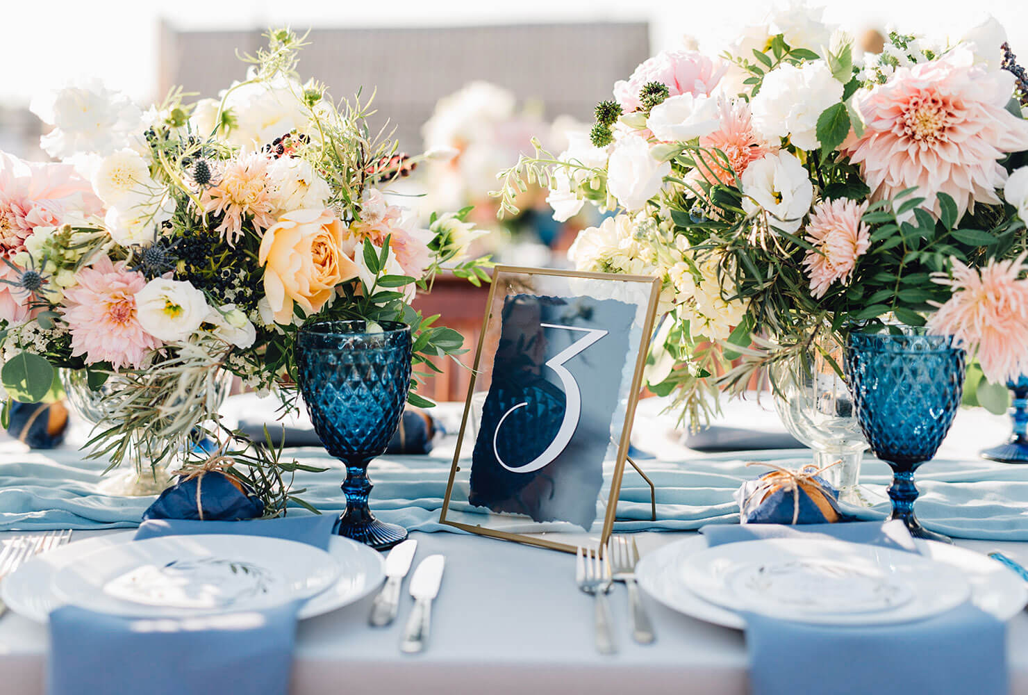 Wedding dinner table decor in a blue and peach color scheme.