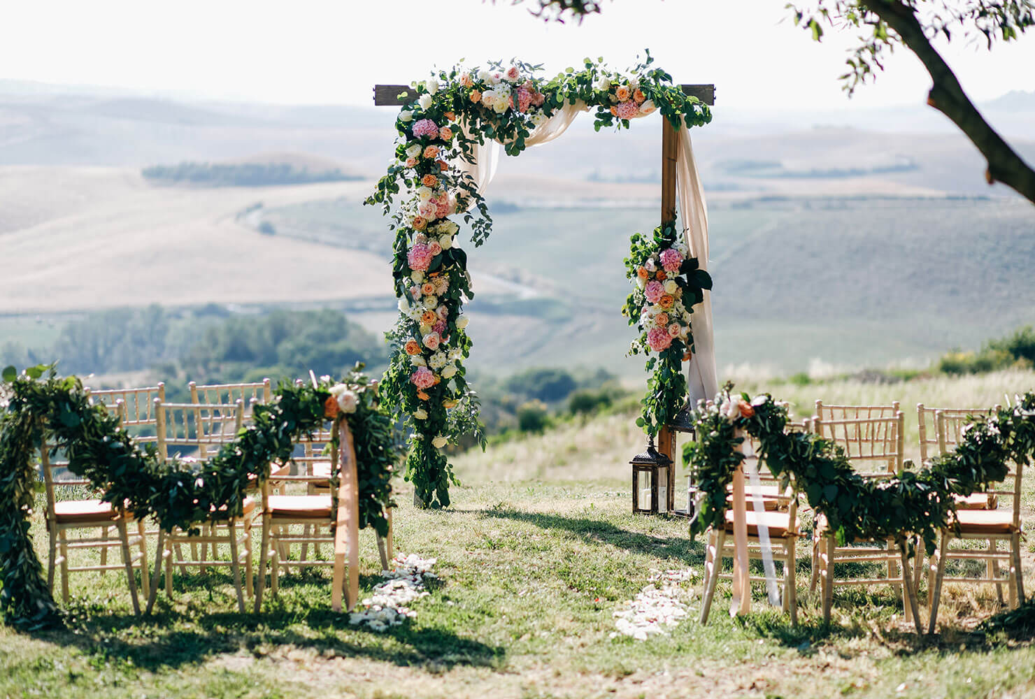 Wedding altar and chairs decorated with vines, florals and drapping fabric.