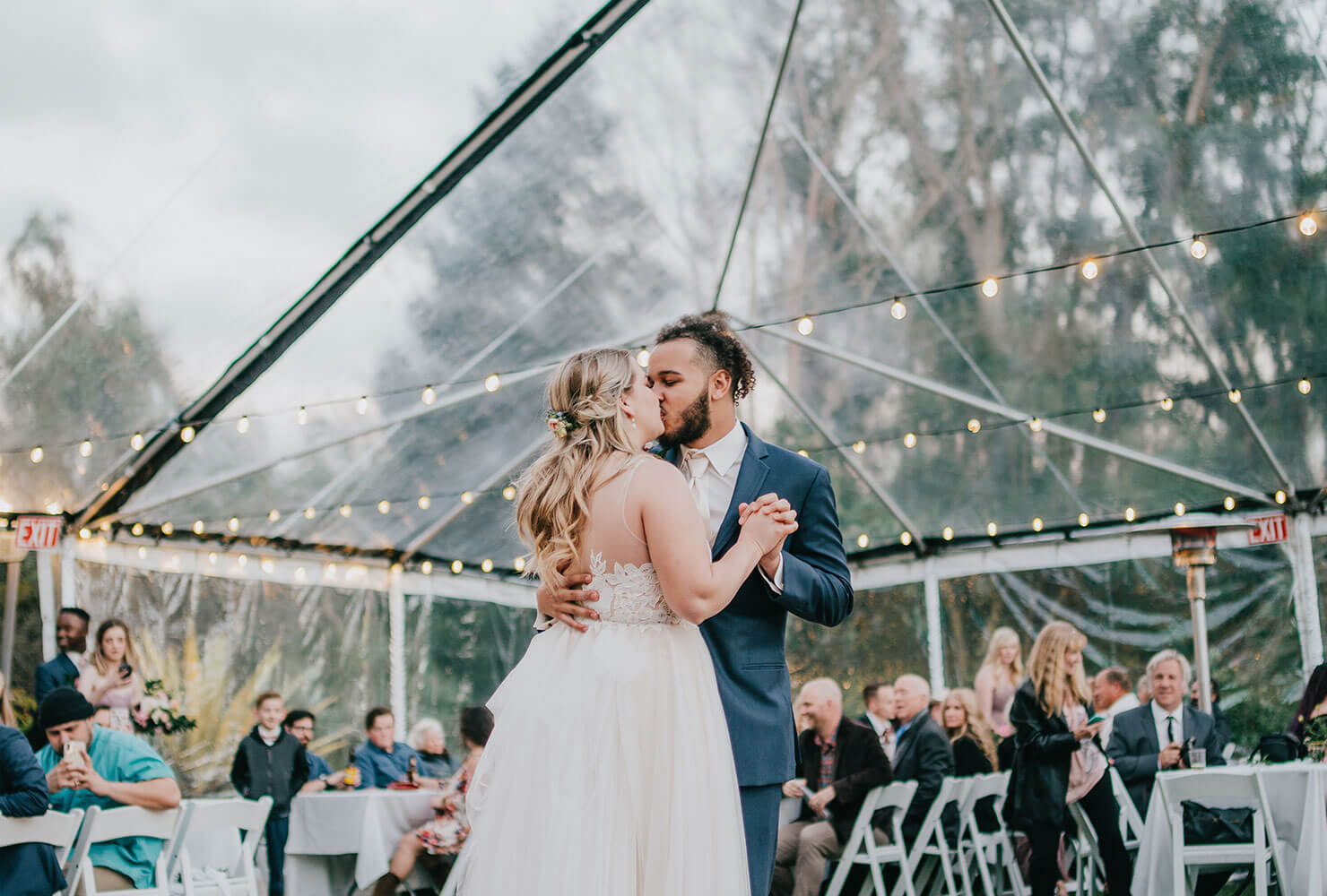 Couple during their first dance under a clear tent surrounded by guests.