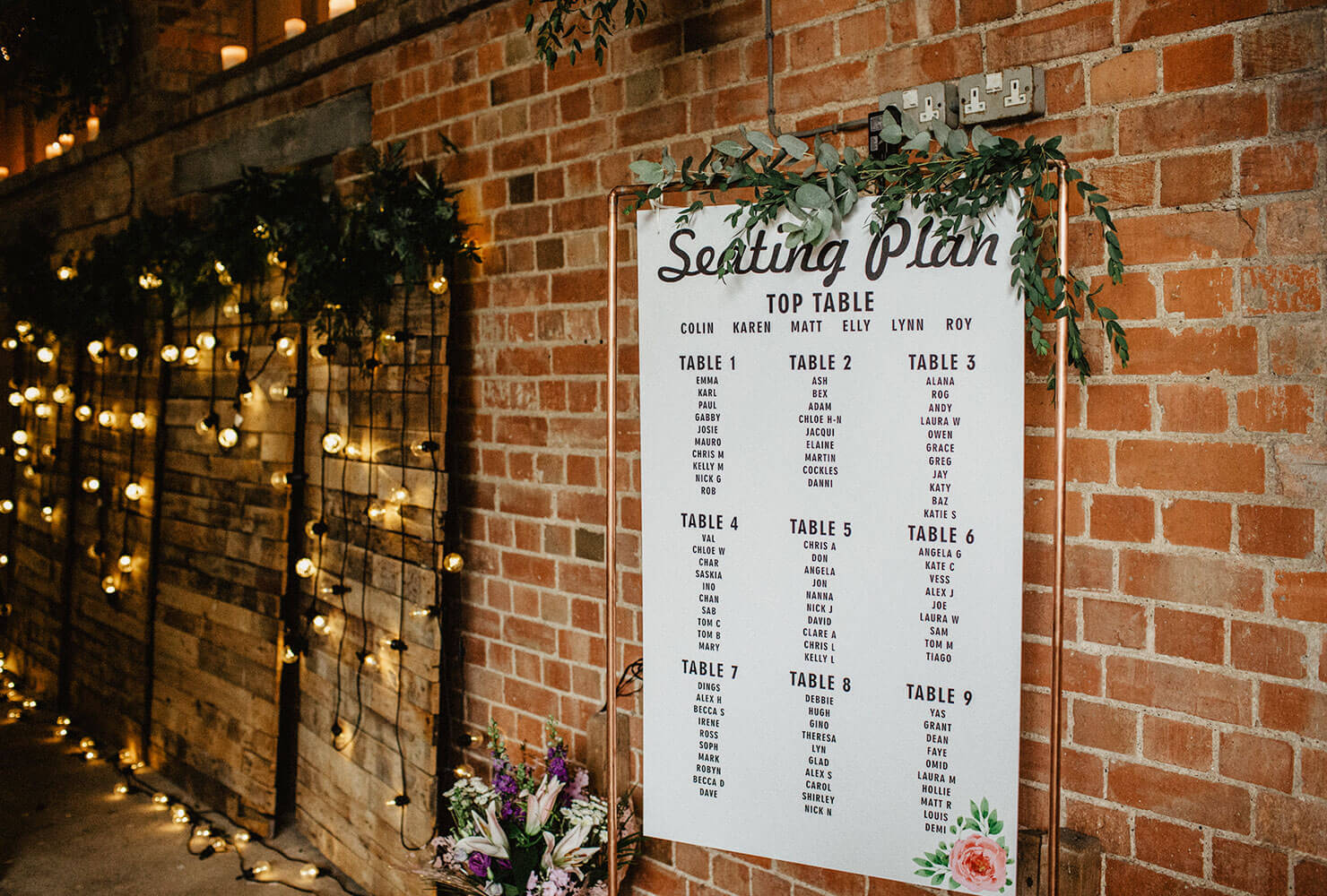 Wedding seating chart on a brick wall decorated with vines and market lights.