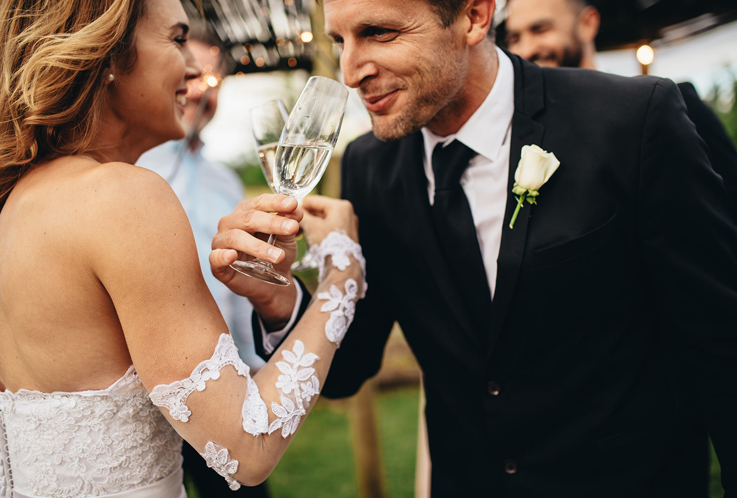 A bridge and groom sip champagne with the arms interlocked. arms