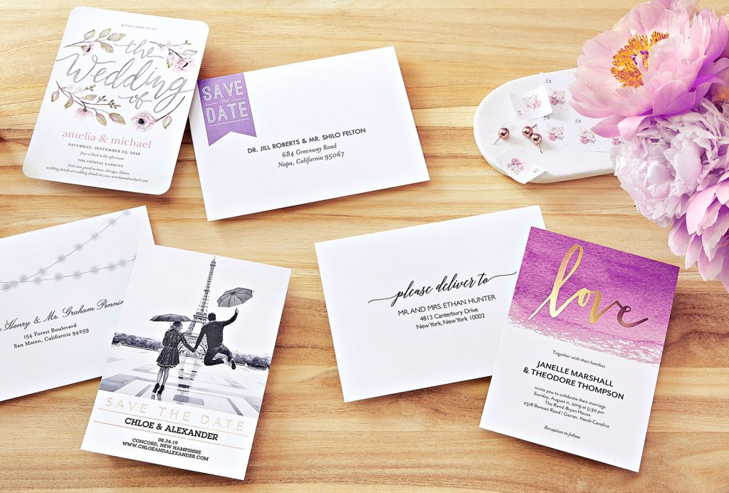 Purple wedding stationery suite next to flowers on a table.