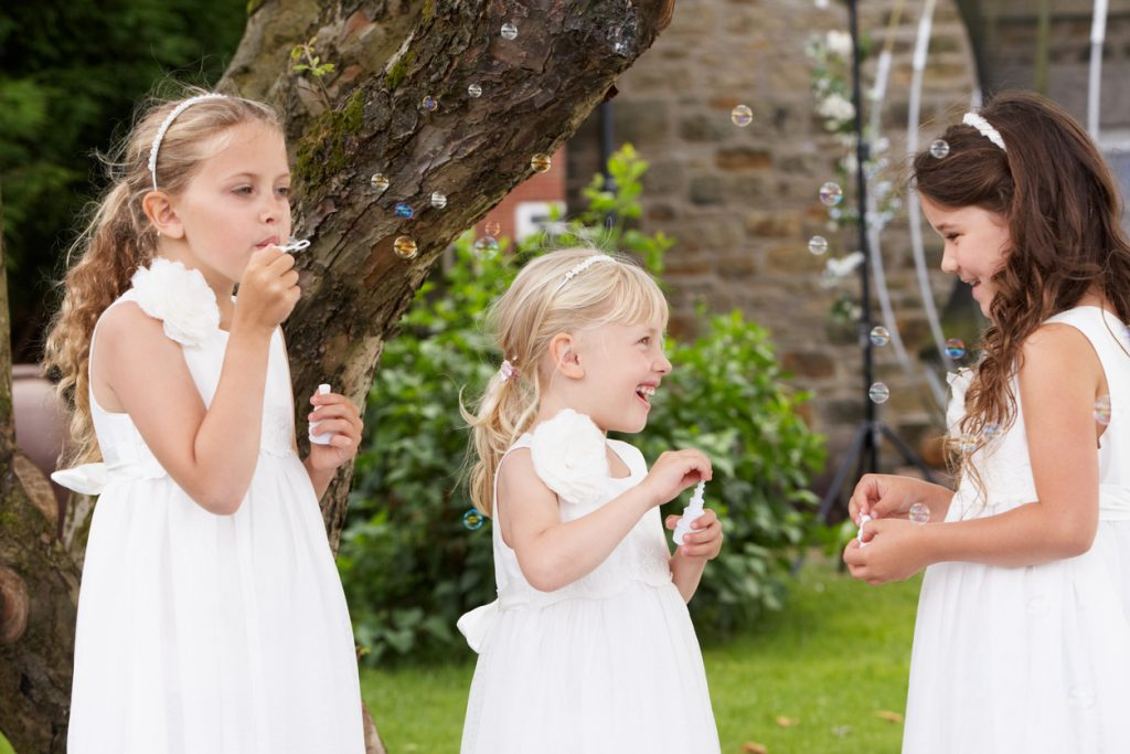 Group Of Flower Girls Having Fun Blowing Bubbles In Garden.