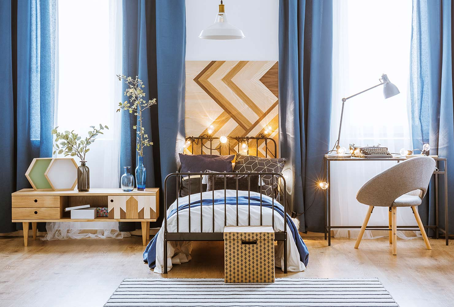 Wooden headboard and blue curtains.