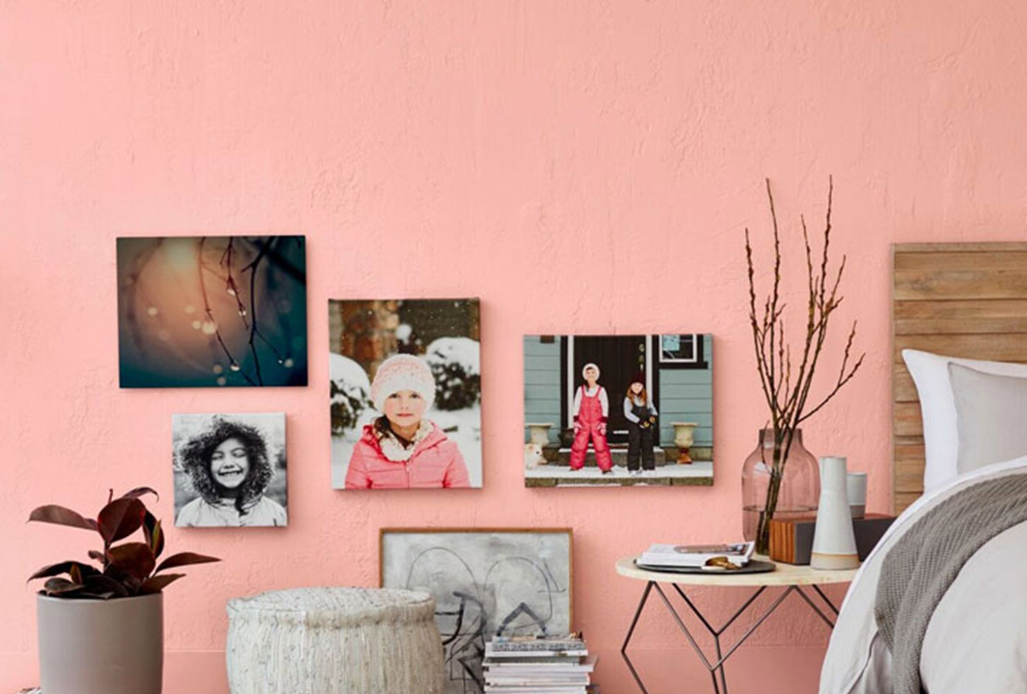 Canvas prints hanging on pink wall.