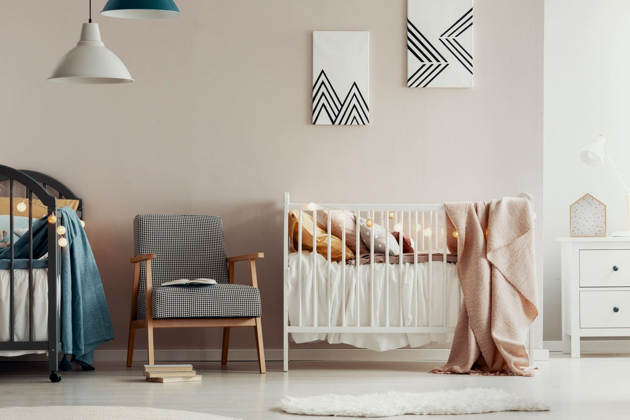 Fashionable retro armchair between two wooden cribs in cute twins nursery
