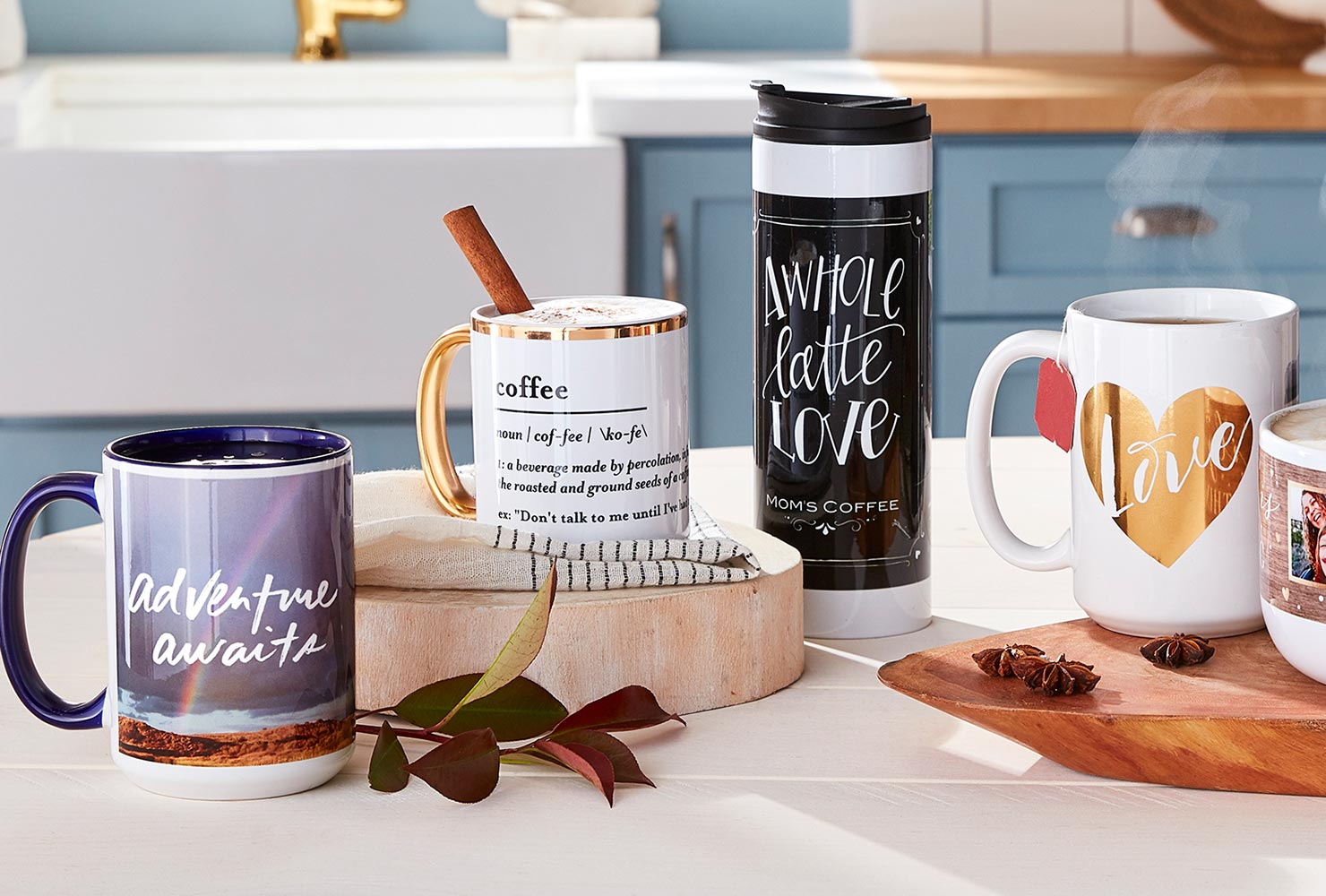 Coffee mugs and tumbler with quotes on table.