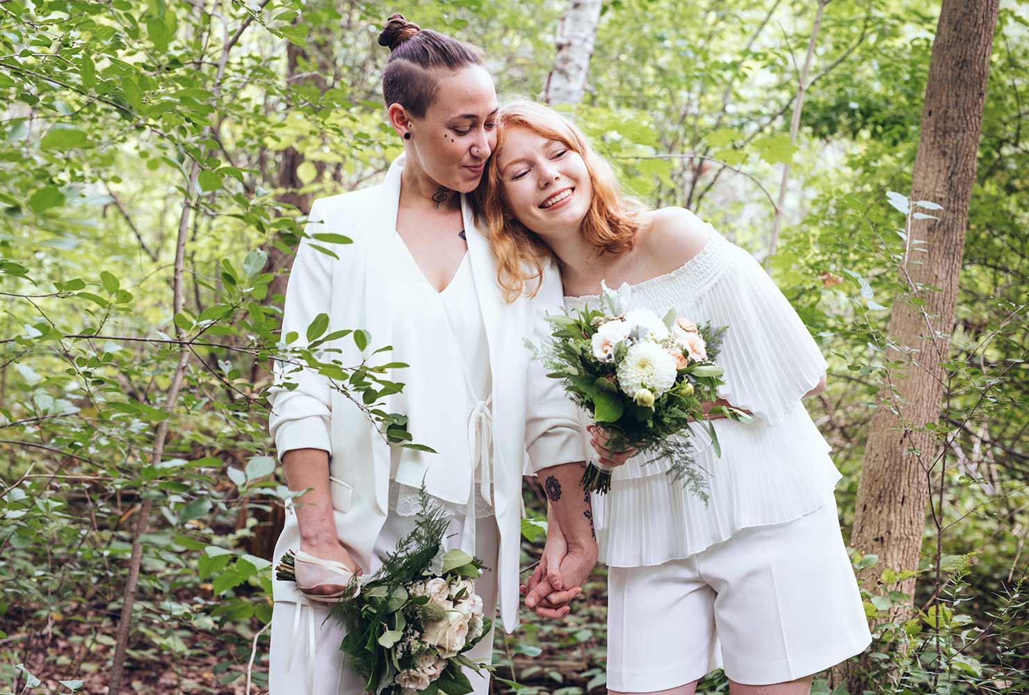 Two brides smiling at wedding in nature