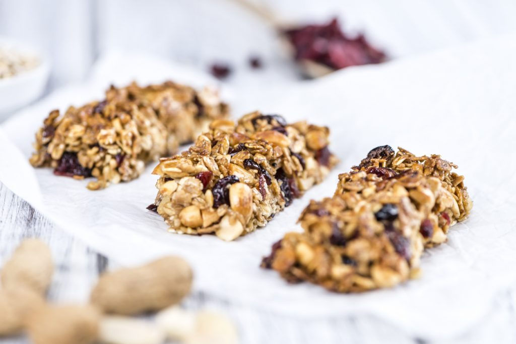 Homemade Granola Bars with Peanuts and Cranberries (selective focus) as detailed close-up shot.
