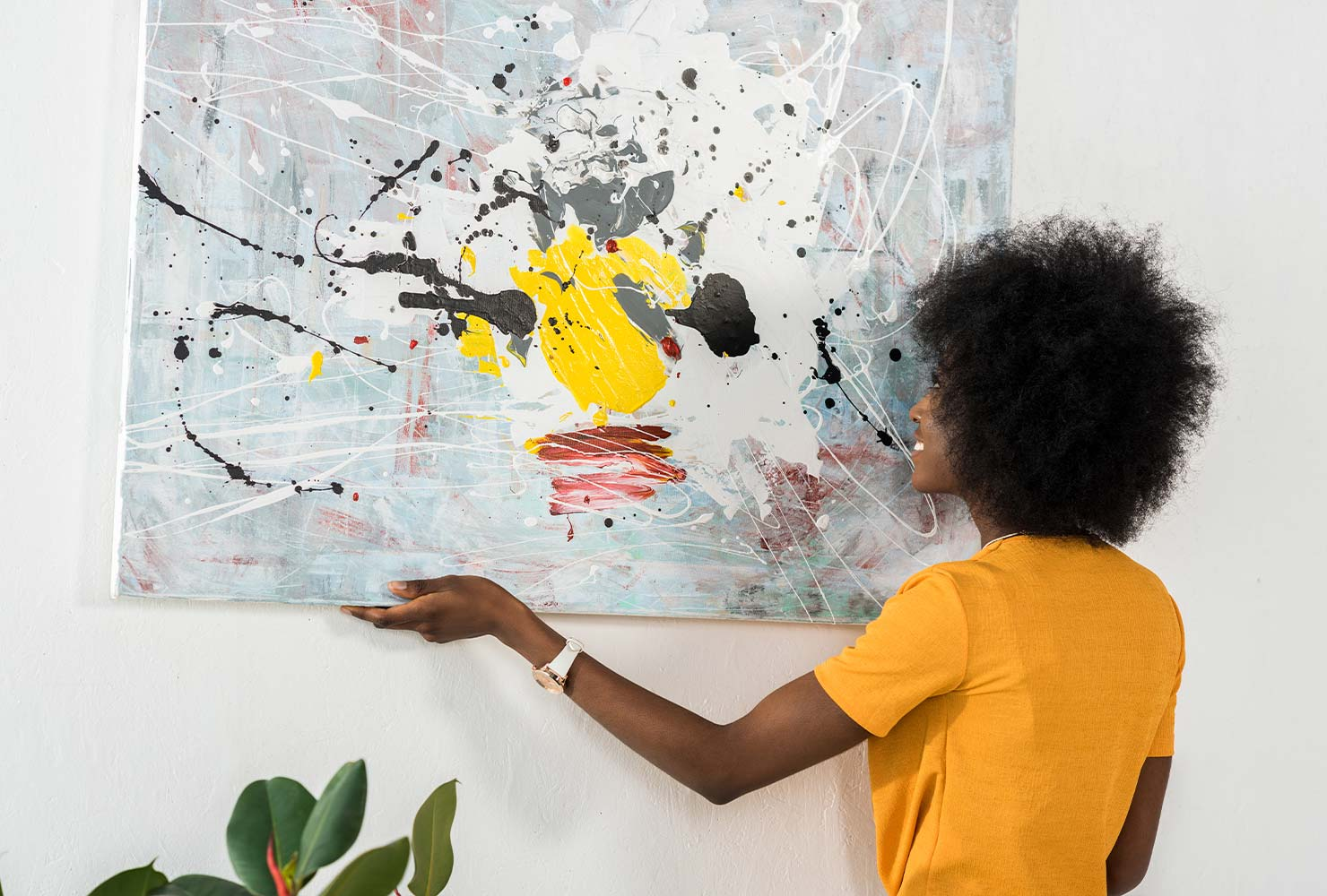 Woman hanging a painted canvas.