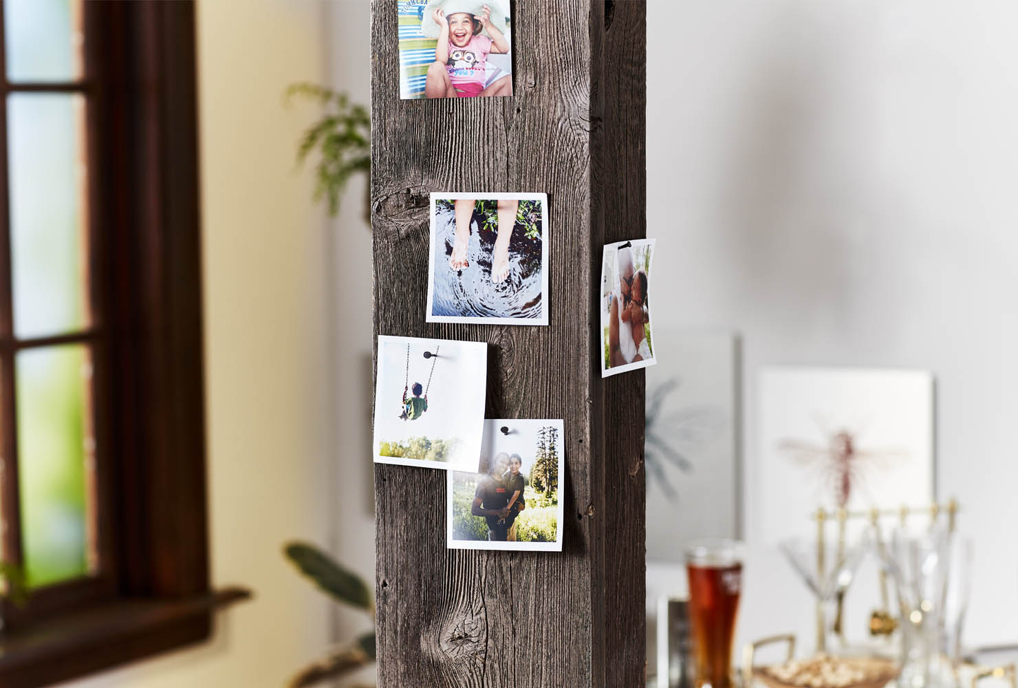 Square photo prints pinned on wooden post.