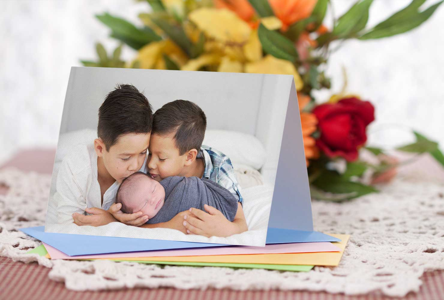 Folded photo card of two young boys kissing newborn boy