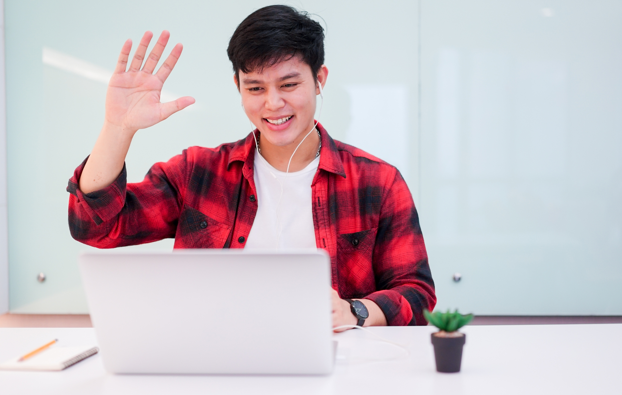 young man wearing earphone and greeting on video conference