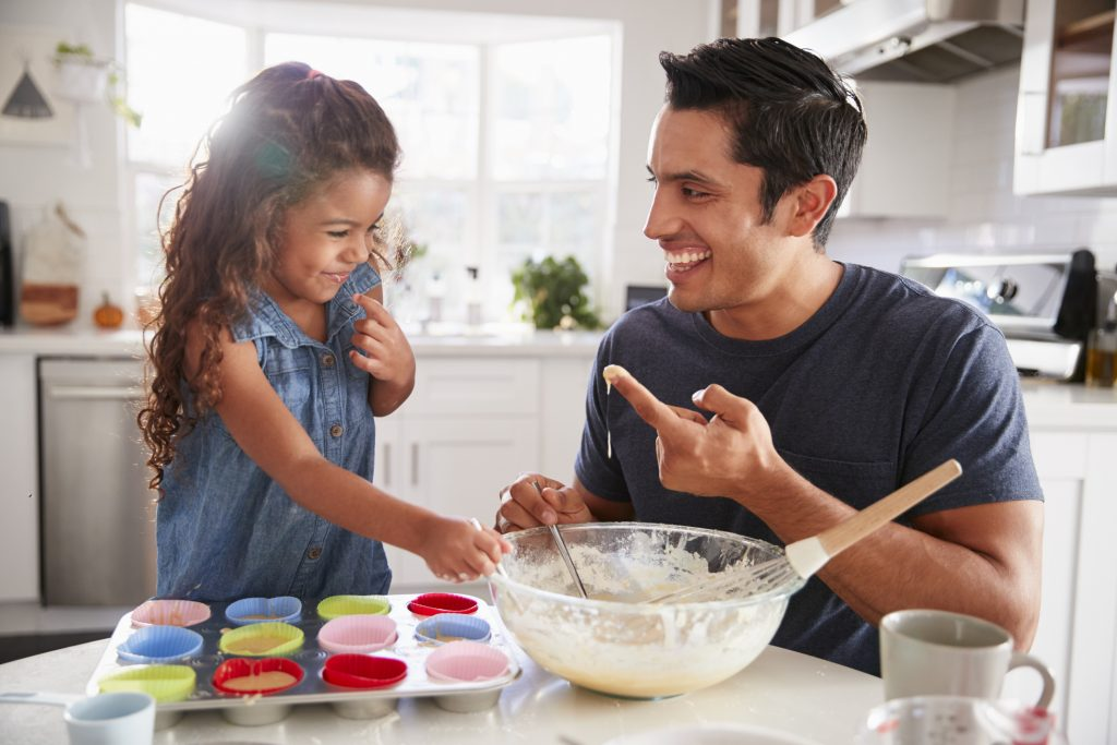 young girl and dad baking cupcakes