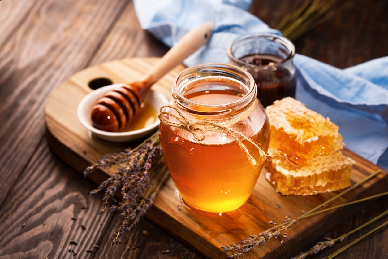 Honey in jar and bunch of dry lavender