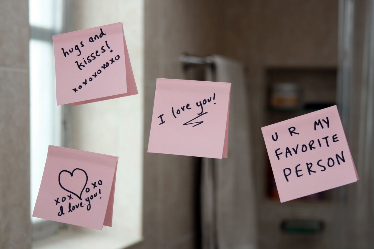 Love notes on sticky paper stuck up on a mirror