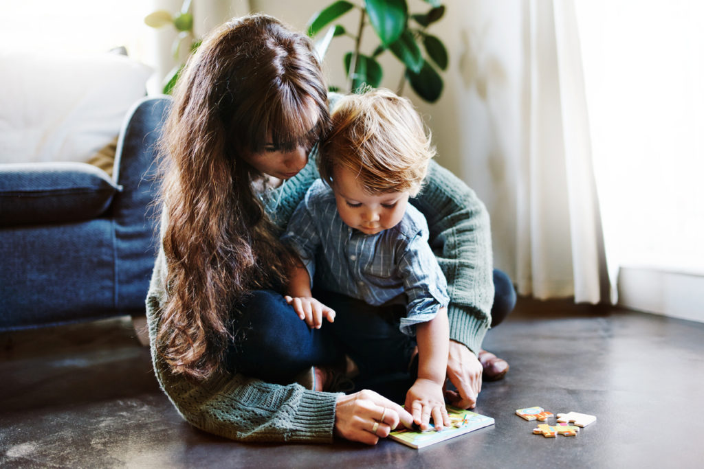 Mom and child playing with puzzles learning how to piece things together