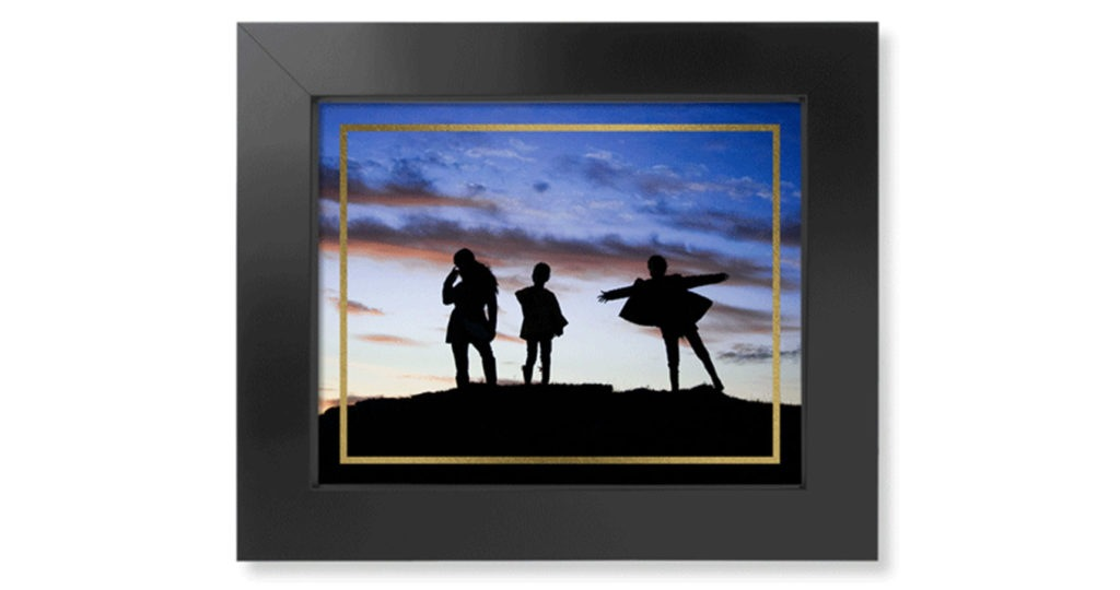 Framed art print with gold foil border around artistic photo and displayed in a dark wood picture frame