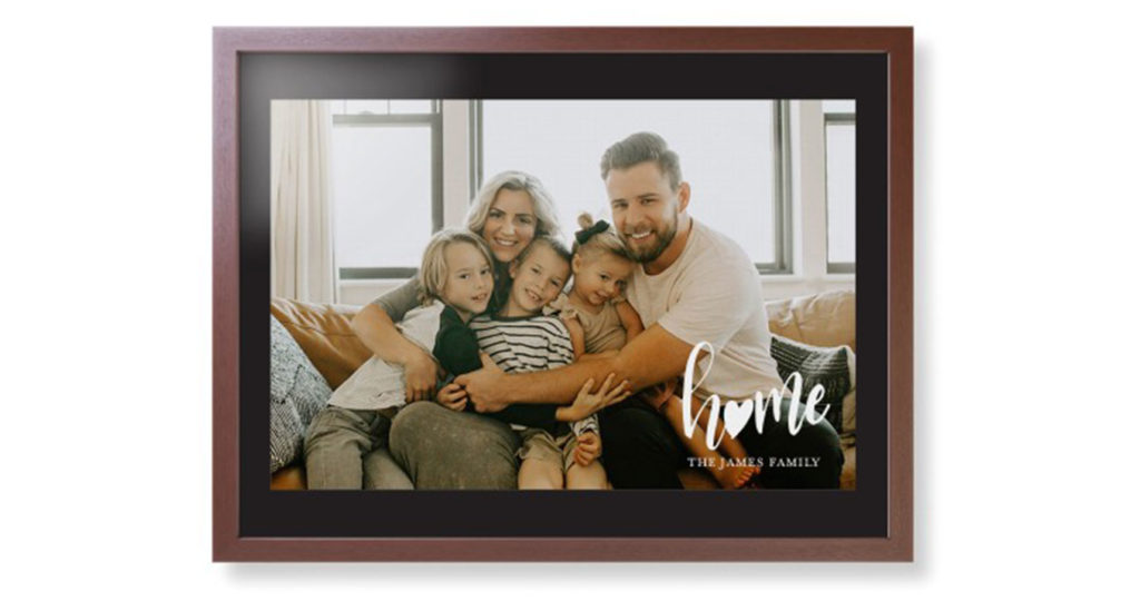 Large framed print with home caption over family photo and set in a wooden picture frame