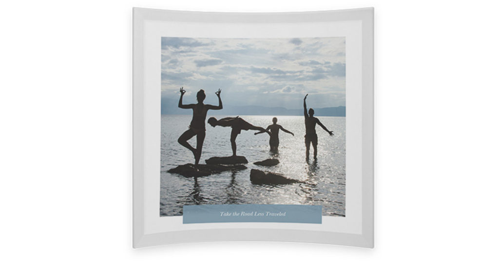 Glass photo print with picture of family in the ocean and a rectangular photo caption at the bottom of the print