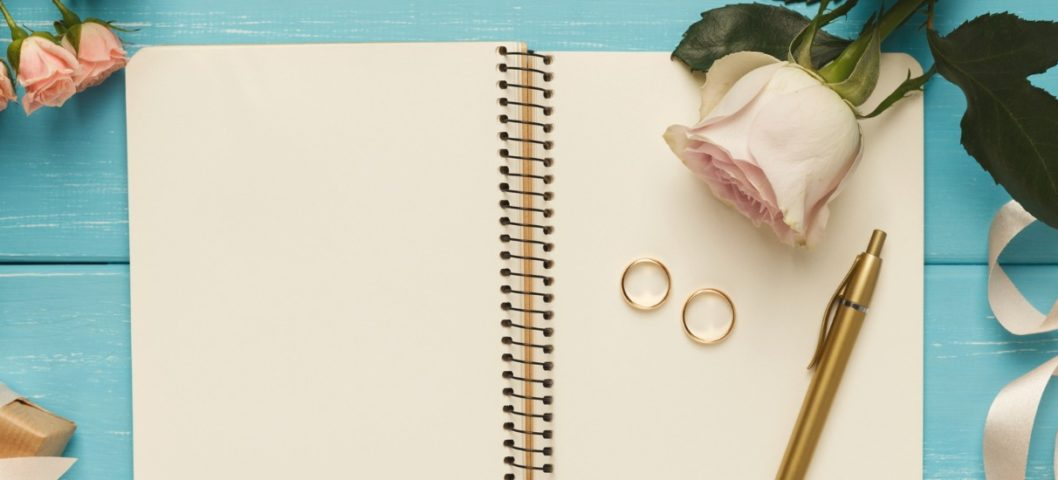 Wedding planning with roses, ribbons, wedding rings, notebook, and pen